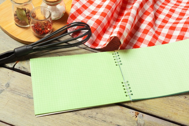 Blank sheet of opened notepad and kitchen utensils on  table with tablecloth