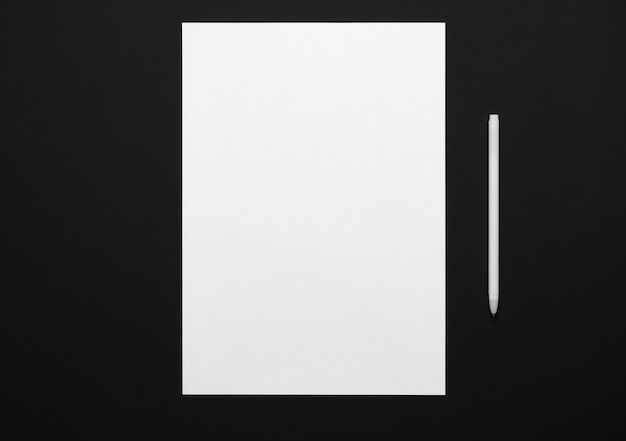 A blank sheet of paper and a pen on a black table, top view - template for any text or inscription