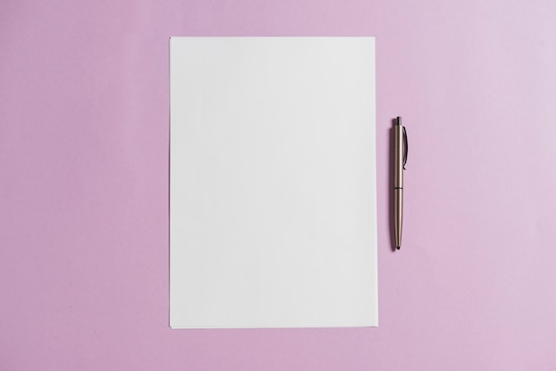 Blank sheet of paper and pen on pink backdrop