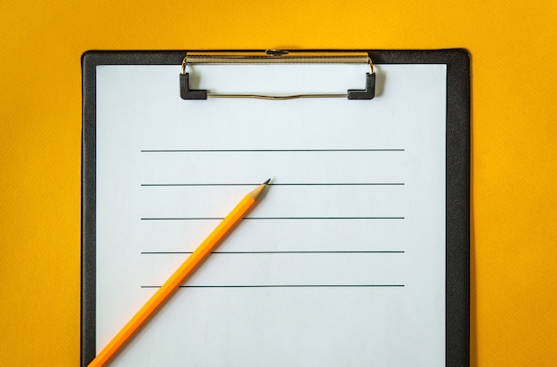 Blank sheet of paper and a pencil for writing on yellow office desk