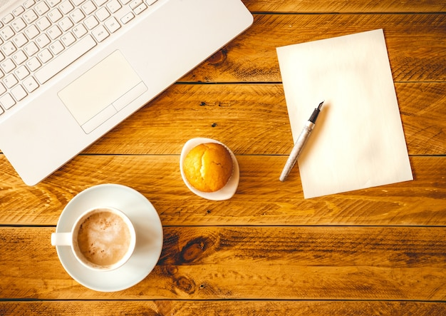 A blank sheet of paper with pen on a wooden work table with a coffee cup and cake.