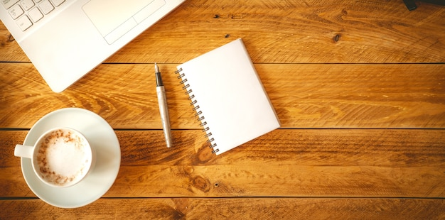 A blank sheet of paper with pen on a wooden work table with a coffee cup.