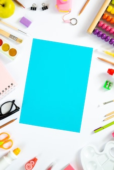 Blank sheet of paper with school accesorries. flat lay. copy space