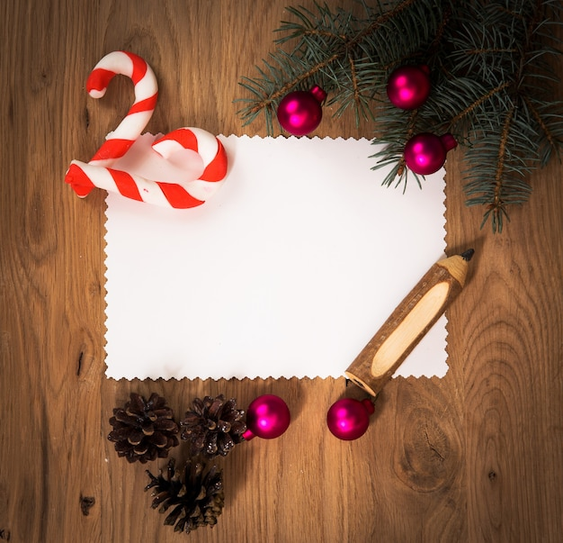 Blank sheet of paper on the wooden floor with a pencil and christmas decorations