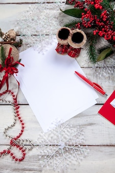Foglio di carta bianco sul tavolo di legno con una penna e decorazioni natalizie.