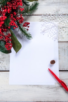 Blank sheet of paper on the wooden table with a pen and  christmas decorations.