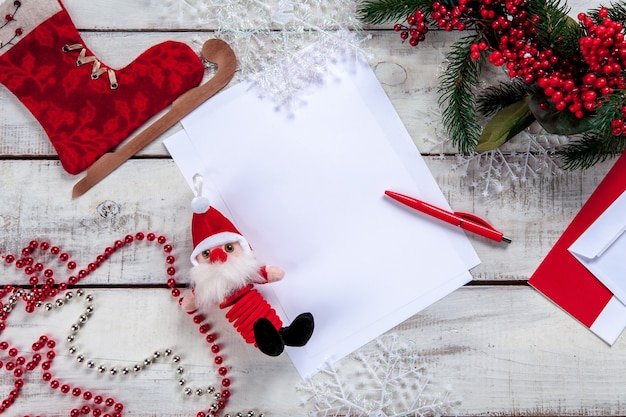 The blank sheet of paper on the wooden table with a pen and christmas decorations.