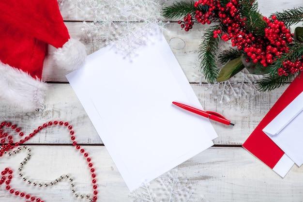 Foglio di carta bianco sul tavolo di legno con una penna e decorazioni natalizie