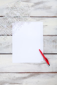 The blank sheet of paper on the wooden table with a pen.
