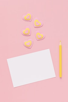 Blank sheet of white paper, yellow pencil, pink and yellow hearts on a pink background, happy valentines day. place for text.