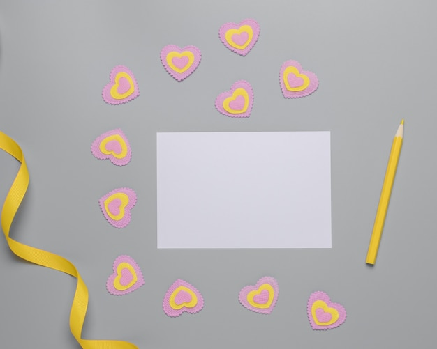 Blank sheet of white paper, yellow ribbon, yellow pencil, pink and yellow hearts on gray background, happy valentines day. place for text.