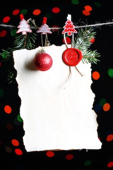 Blank sheet with christmas decor on black surface with lights
