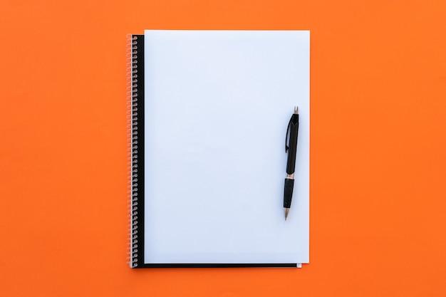 Чистый лист с блокнотом и ручкой на оранжевом фоне.