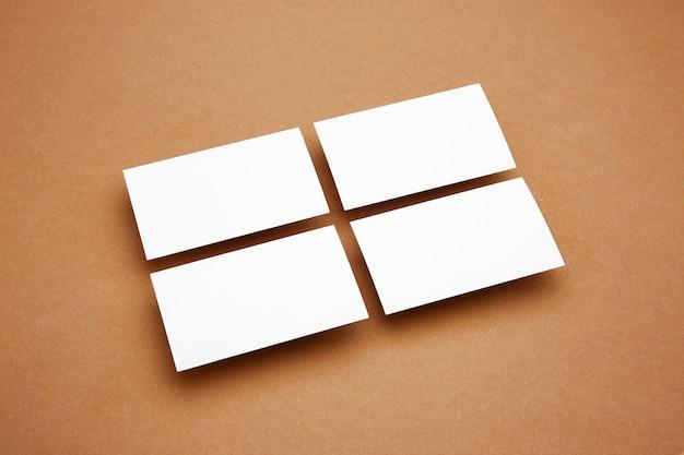 茶色の背景の上に浮かぶ空白のシート、創造的。ホワイトカード。広告用のオフィススタイルのモダンなモックアップ。デザイン、ビジネス、財務のコンセプトのための空白の白いコピースペース。