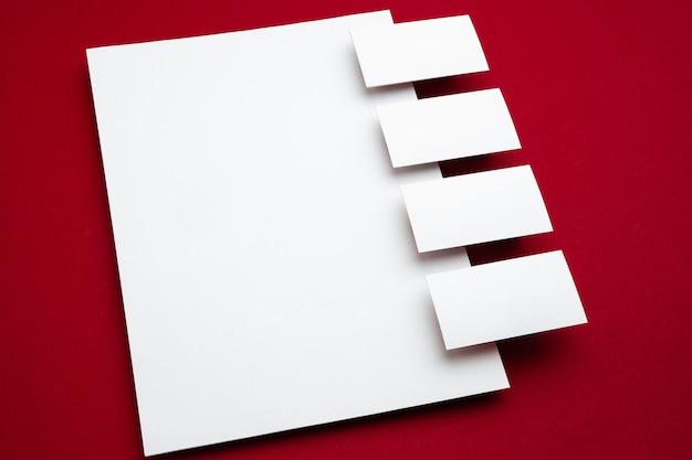 赤い背景の上に浮かぶ空白のシート、創造的。並んでいる白いカード。広告用のオフィススタイルのモダンなモックアップ。デザイン、ビジネス、財務のコンセプトのための空白の白いコピースペース。