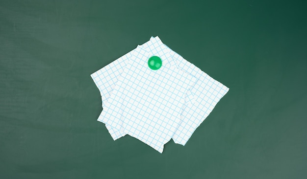 Blank sheets of paper in a cage attached to a green magnetic board,  close up
