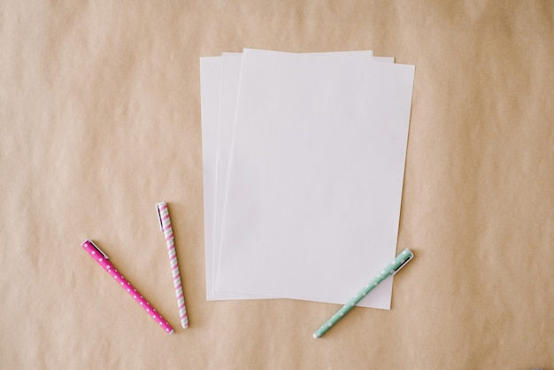 Blank sheets of white paper and colorful pens on a crafting paper