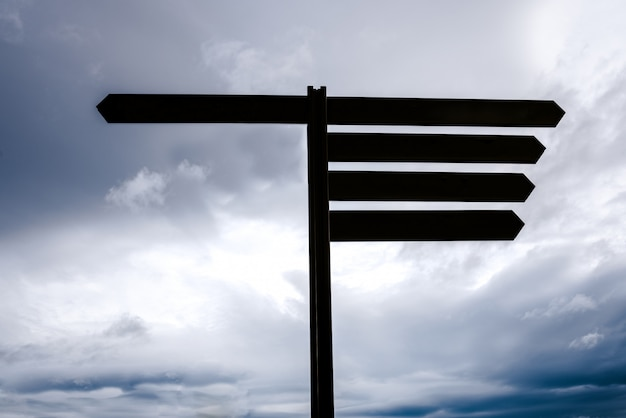 Blank sign pole, empty with space for text, sky background, concept of doubt and choice.