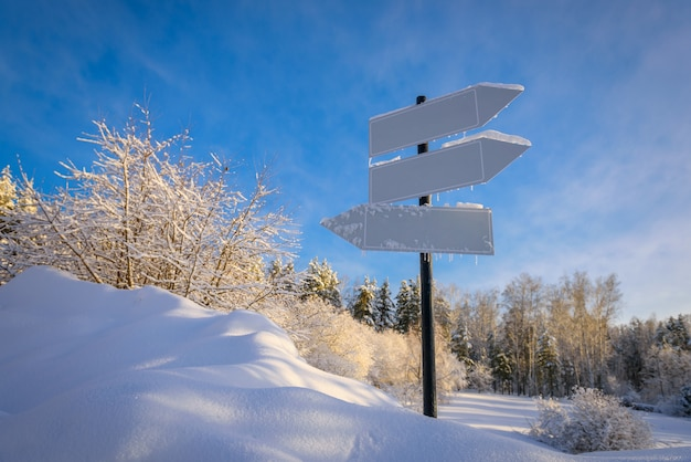Blank signpost with three white arrows against beautiful blue sky in sunny frozen day.