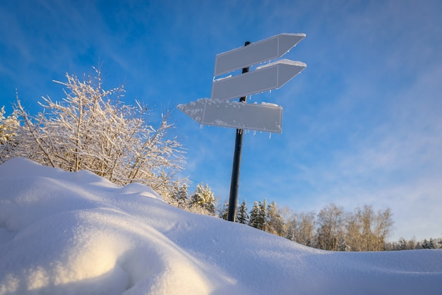 Blank signpost with three white arrows against beautiful blue sky in sunny frozen day