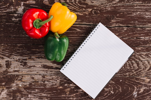 Blank single line spiral notepad with red; yellow and green bell peppers on wooden texture backdrop