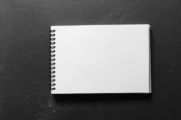 Blank sketchbook with white pages isolated on black