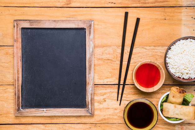 Blank slate near the chopsticks; spring rolls; rice and sauces on wooden desk
