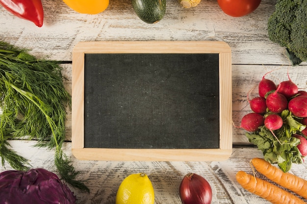 Blank slate surrounded by various healthy food on wooden surface