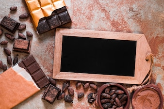 Blank slate tag with chocolate bar, cocoa beans and powder on table