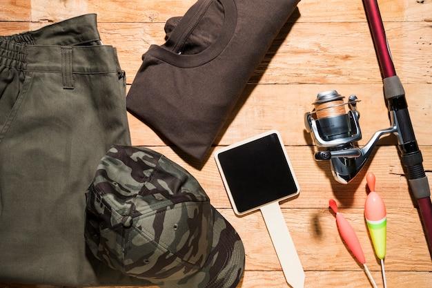 空白の小さなプラカード。釣りフロート。釣り竿と木製の机の上の男性服
