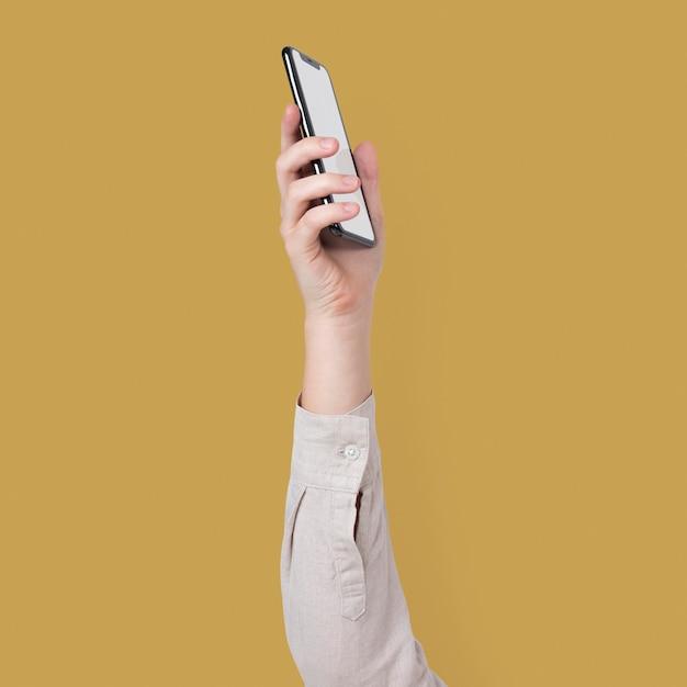 Schermo dello smartphone vuoto isolato in studio con la mano alzata