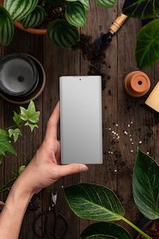 Schermo dello smartphone vuoto in un negozio di piante