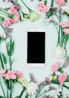Blank smartphone surrounded with fresh limonium; carnations and eustoma flowers against blue background