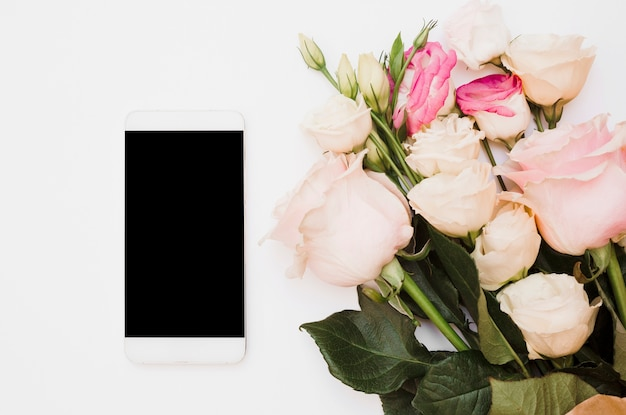 Smartphone in bianco con bouquet di fiori su sfondo bianco