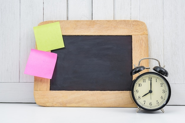 Blank space chalkboard, alarm clock and blank sticky note, post note on office desk white