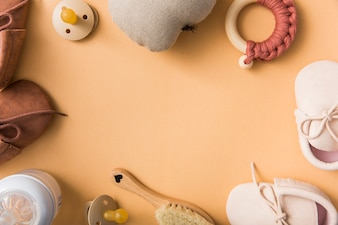 Blank space for text with pair of shoes; pacifier; stuffed pear; brush; milk bottle on an orange backdrop