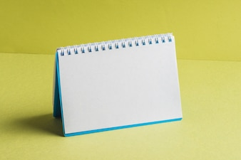 Blank spiral book on yellow background
