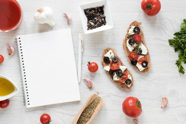 Blank spiral diary and bruschetta with ingredient on wooden table