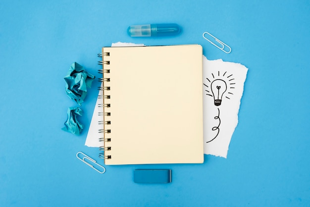 Blank spiral diary and stationery supplies with hand drawn light bulb on white card paper over blue surface