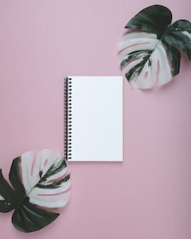 空白のスパイラルノートとパステルの葉のモンスター