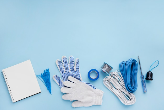 Blank spiral notebook and electrician equipment on blue surface