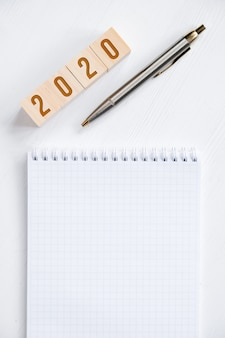 Blank spiral notebook, fountain pen, wooden cubes with numbers new year
