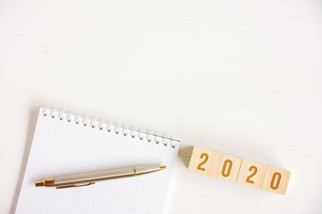 Blank spiral notebook, pen, cubes with numbers new year