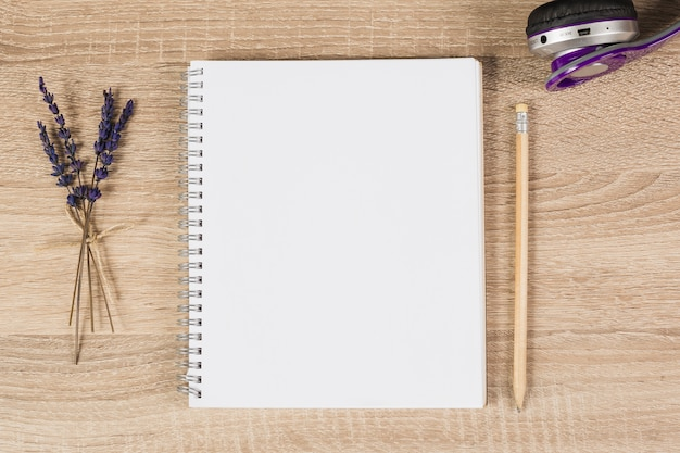 Blank spiral notebook; pencil; headphone and lavender twigs on wooden background