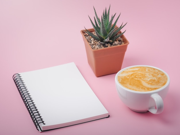 Blank spiral notebook on pink background and cup of latte coffee