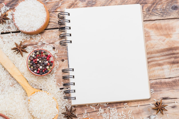 Blank spiral notebook; raw rice and dry spices on wooden wallpaper