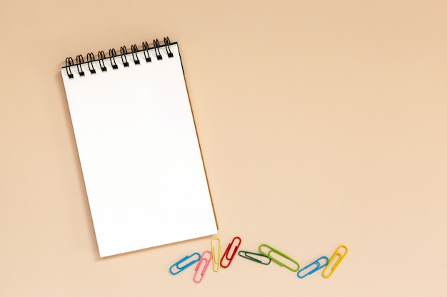 Blank spiral notebook with colorful clips on table.