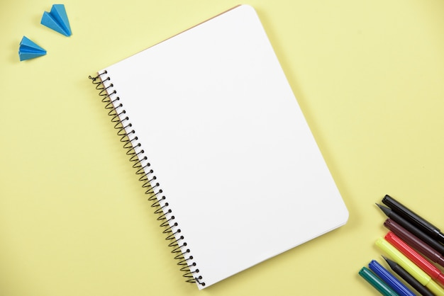 Blank spiral notebook with colorful felt tip pen on yellow backdrop