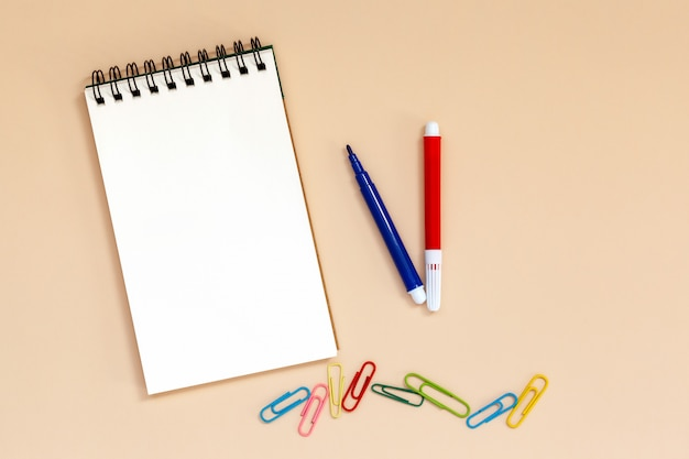 Blank spiral notebook with colorful pens and clips on table.