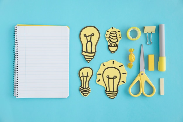 Blank spiral notebook with paper light bulbs and stationery on blue background